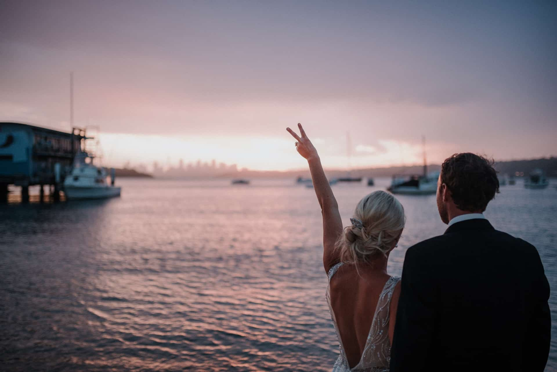 brides makes a peace symbol with her left hand as they look out towards sunset at watsons bay